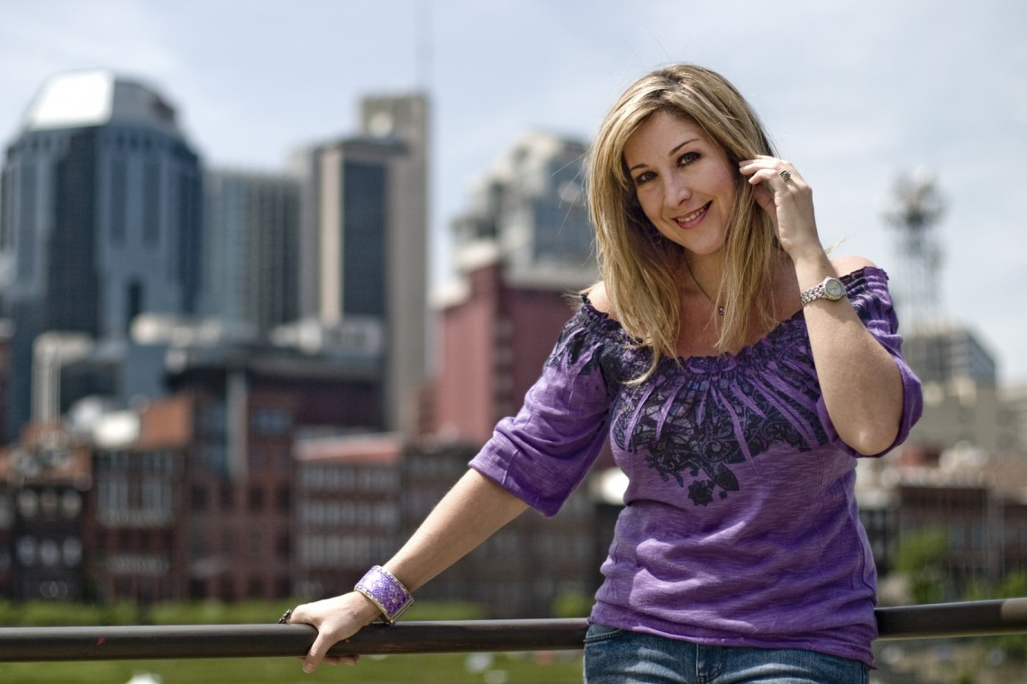 Holly leaning against a railing with downtown Nashville as a backdrop