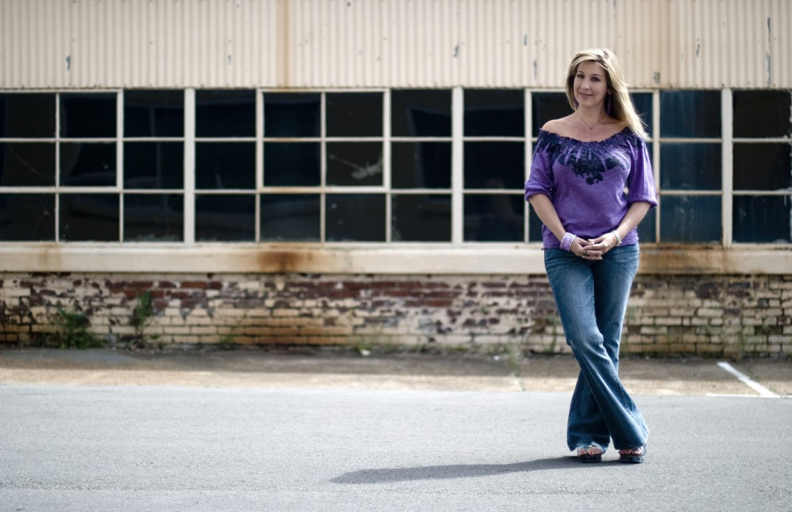 Holly standing with her feet crossed and a warehouse behind her