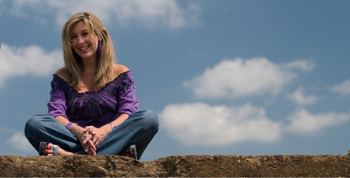 Holly sitting on a stone wall with the blue sky behind her