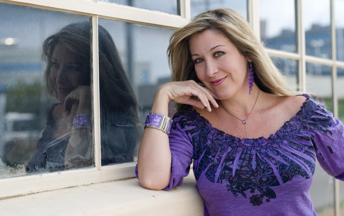 Holly leaning against a window sill with her reflection in the glass behind her